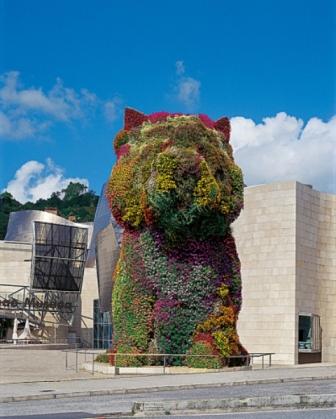 """""""Puppy"""" es un simpático Fox terrier de 12 m de altura creado en 1992 por el artista Jeff Koons que se encuentra junto al edificio creado por Frank Gehry. Está formado por una estructura de acero inoxidable cubierta por diferentes especies en flor y en 1997 fue trasladado desde el Museo de Arte Contemporáneo de Australia hasta Bilbao gracias al patrocinio de Hugo Boss."""
