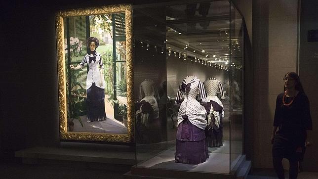 """La muestra """"El Impresionismo y la Moda"""" (a.2012) contó con el patrocinio de LVMH y pudo verse en París, Nueva York y Chicago. En esta imagen de las salas de la exposición en el Museé d'Orsay  se puede ver la obra """"El invernadero"""" (a.1881) en la que el pintor Albert Bartholomé retrata a su esposa luciendo el vestido que puede verse junto al lienzo y que fue donadado al museo en 1991."""