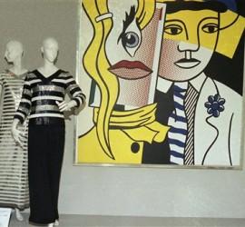 """Modelos de de Yves Saint Laurent junto a la obra"""" Stepping Out"""" (1978 ) de Roy Lichtenstein en la exposición """"Yves Saint Laurent. 25 años de creación"""" en el Museo Metropolitan de Nueva York (a.1983). Esta muestra recibió más de una crítica ya que era la primera vez que un gran museo dedicaba una retrospectiva a un diseñador vivo y en activo."""
